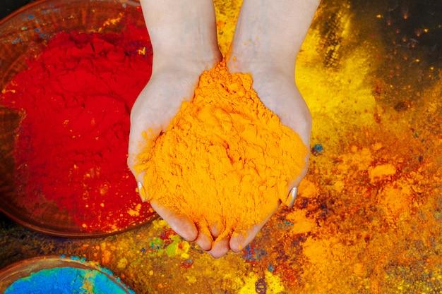 Mani che tengono la vernice in polvere holi, vista dall'alto