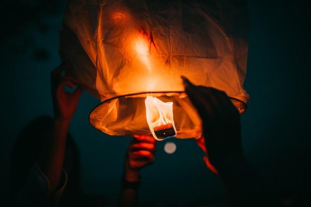 Mani che tengono lanterna volante cinese