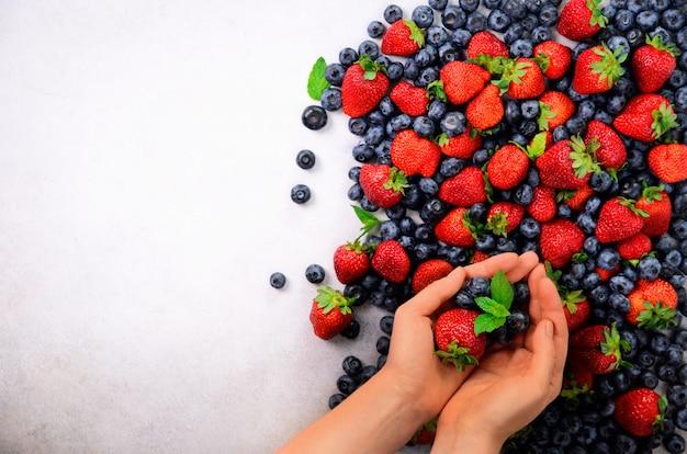 Mani che tengono le bacche fresche. cibo pulito sano, dieta, cibo vegetariano, concetto di disintossicazione.