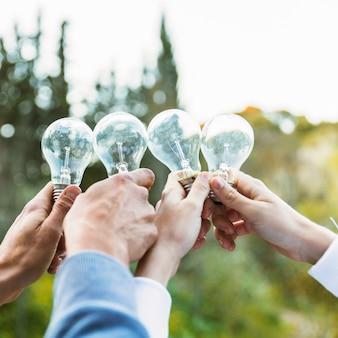 Mani che tengono le lampadine il giorno di ecologia