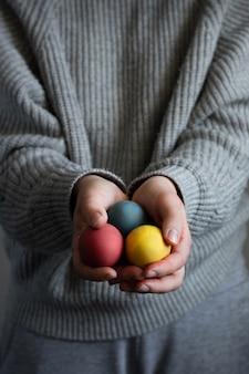 Mani che tengono mazzo di uova di pasqua variopinte