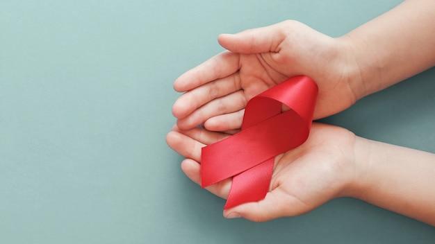 Mani che tengono nastro rosso su fondo rosso, concetto di consapevolezza dell'hiv, giornata mondiale contro l'aids, giornata mondiale dell'ipertensione