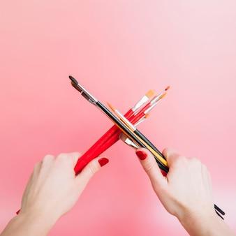 Mani che tengono pennelli