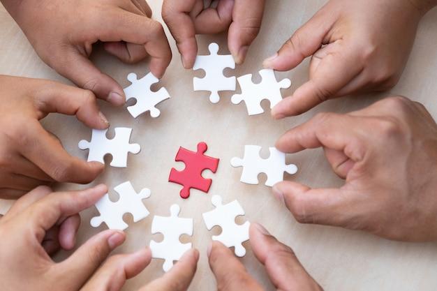 Mani che tengono pezzo di puzzle in bianco con fondo in legno tavolo.