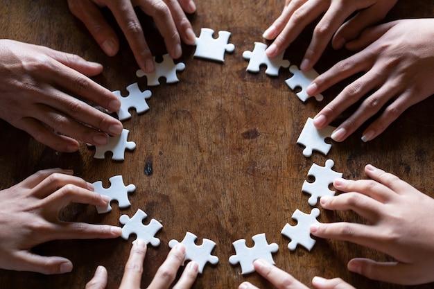 Mani che tengono pezzo di puzzle in bianco su sfondo nero