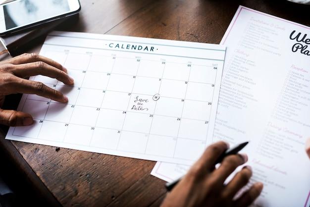 Mani che tengono preparazione di informazioni di lista di controllo del pianificatore di cerimonia nuziale