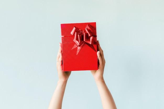 Mani che tengono regalo rosso su sfondo chiaro