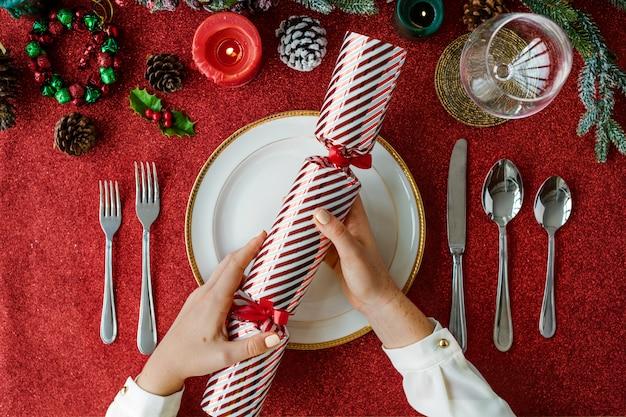 Mani che tengono regalo sulla festa di vacanza di natale sul tavolo rosso