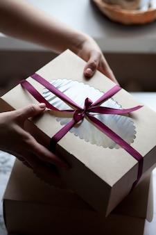 Mani che tengono scatola festiva con un inchino