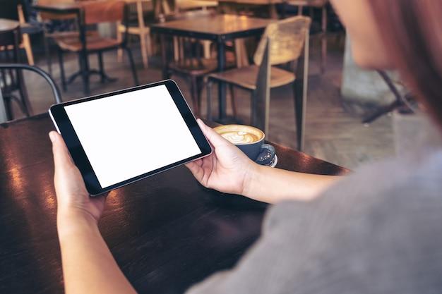 Mani che tengono tablet pc nero con uno schermo bianco vuoto con una tazza di caffè