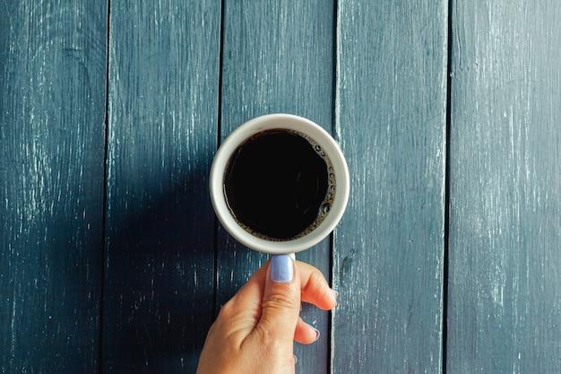Mani che tengono tazza della bevanda calda sulla tavola di legno