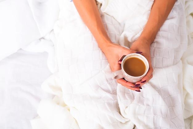 Mani che tengono tazza di caffè calda