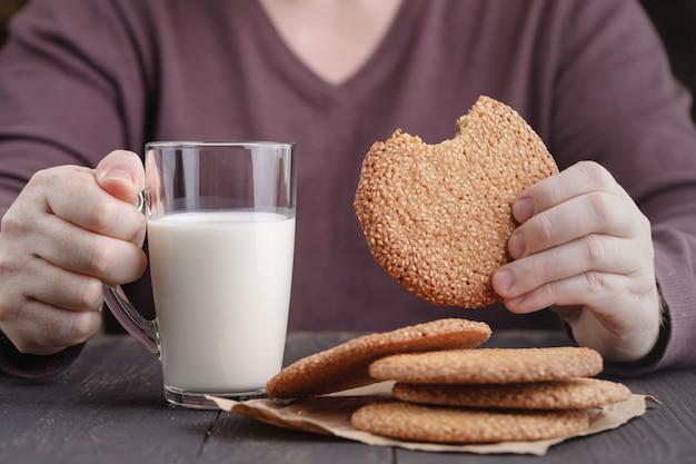 Mani che tengono tazza di caffè e biscotti sulla tavola nera