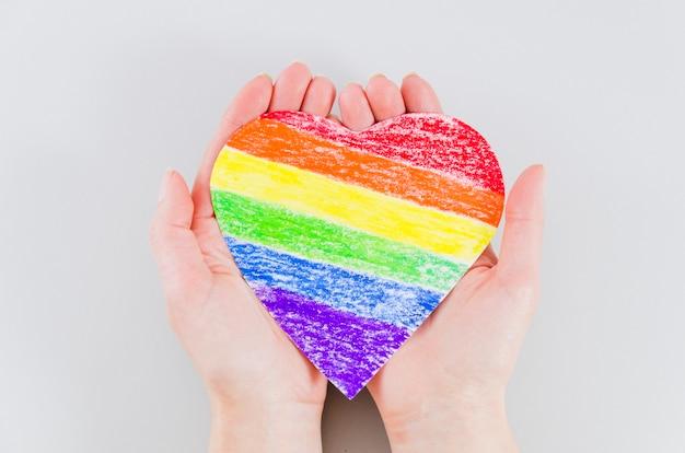 Mani che tengono un cuore con i colori della bandiera del giorno dell'orgoglio