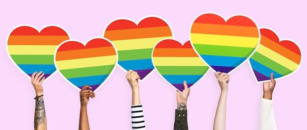 Mani che tengono un grafico del cuore dell'arcobaleno del lgbt
