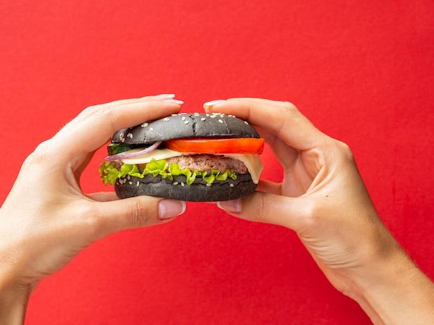 Mani che tengono un hamburger su fondo rosso