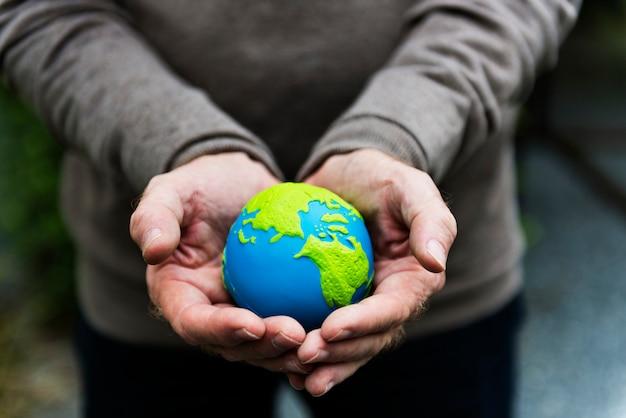 Mani che tengono un pianeta terra globo di argilla