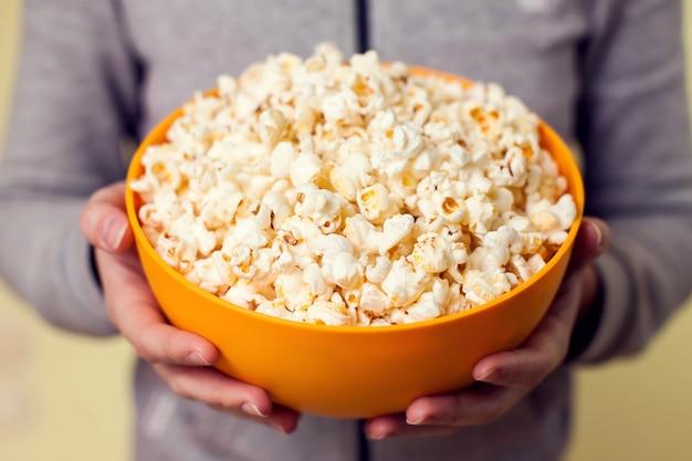 Mani che tengono una ciotola di popcorn