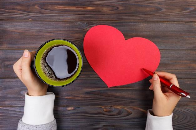 Mani che tengono una tazza di caffè e scrivere san valentino.
