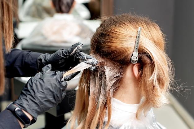 Mani che tingono i capelli della donna