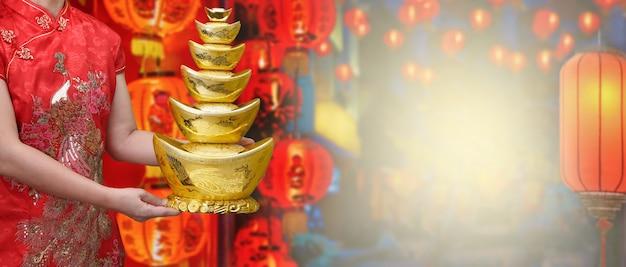 Mani cinesi della donna del lingotin dell'oro del nuovo anno