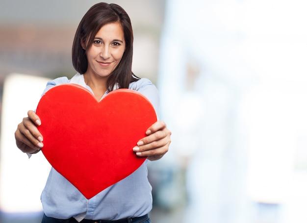 Mani close-up di donna che mostra un cuore rosso