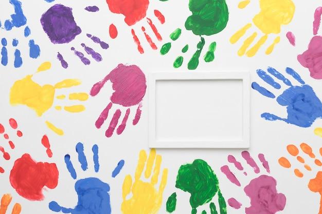 Mani colorate su sfondo bianco con cornice vuota