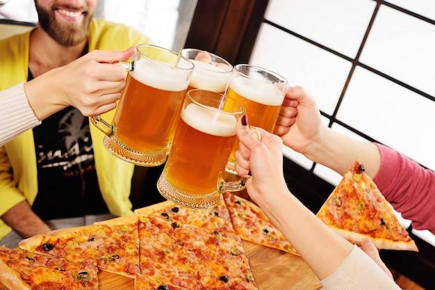 Mani con bicchieri di birra close-up su uno sfondo di pizza.