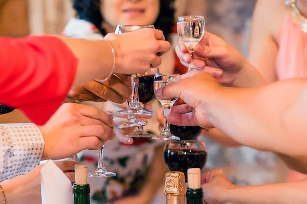 Mani con bicchieri di vino e vodka gruppo di amici a una festa