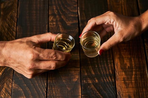 Mani con bicchierini tostatura. concetto di alcolismo e dipendenza.