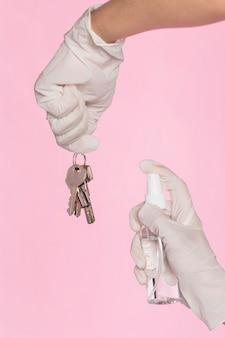 Mani con guanti chirurgici che disinfettano le chiavi
