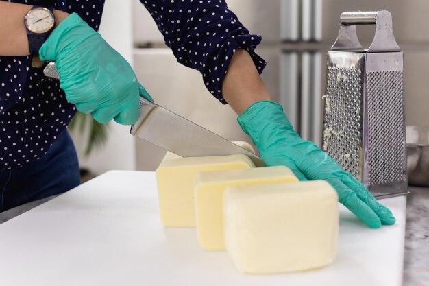Mani con il coltello che taglia un formaggio sul bordo bianco.