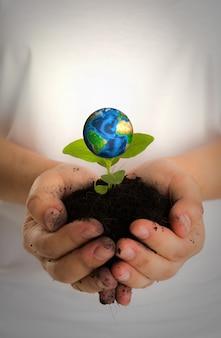 Mani con il pianeta terra e la terra sotto