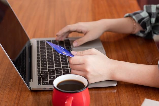 Mani con la carta di credito della tenuta facendo uso del computer portatile per l'e-introduzione sul mercato o il concetto online di compera a casa