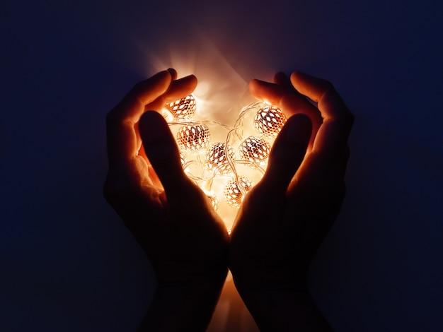 Mani con lampadine a forma di cuore.