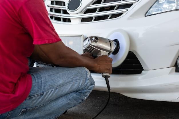 Mani con lucidatrice orbitale lucidatura auto bianca. dettagli auto e concetto di lavaggio.