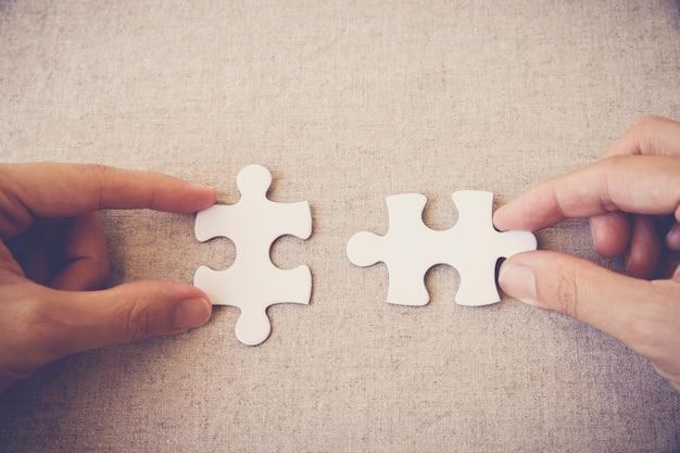 Mani con pezzi di un puzzle