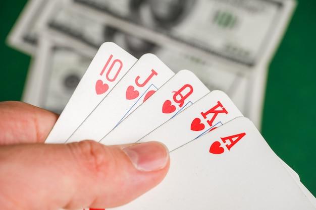 Mani con scala reale di cuori durante il poker con dollari sul tavolo verde.