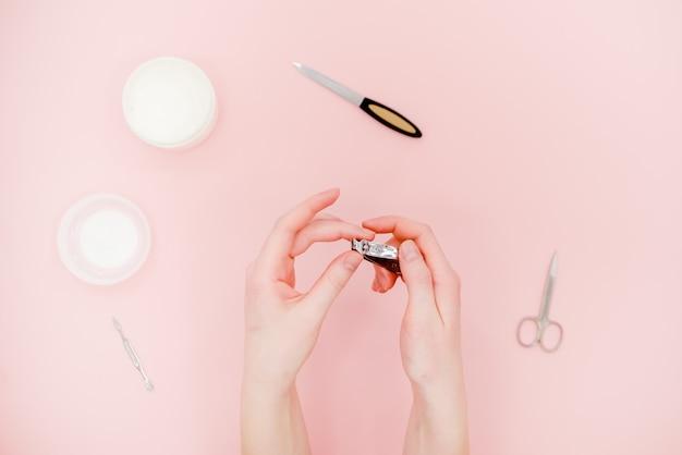 Mani con vasetto bianco crema, kit manicure, forbici. concetto di cura della pelle