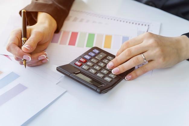 Mani contando sulla calcolatrice con penna
