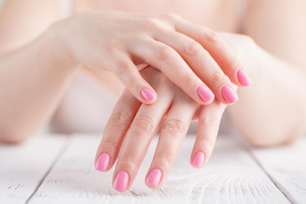 Mani curate francesi della donna contro il corpo in camicia bianca, primo piano