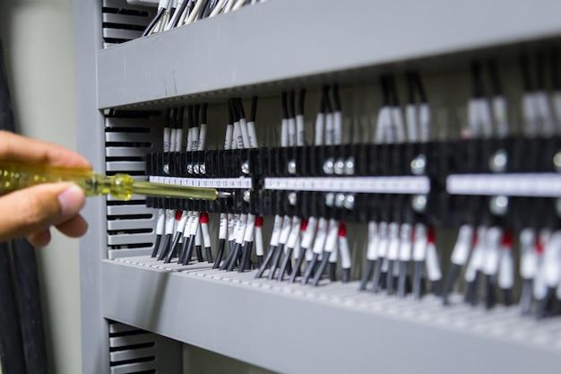Mani degli elettricisti che verificano corrente elettrica nel pannello di controllo.