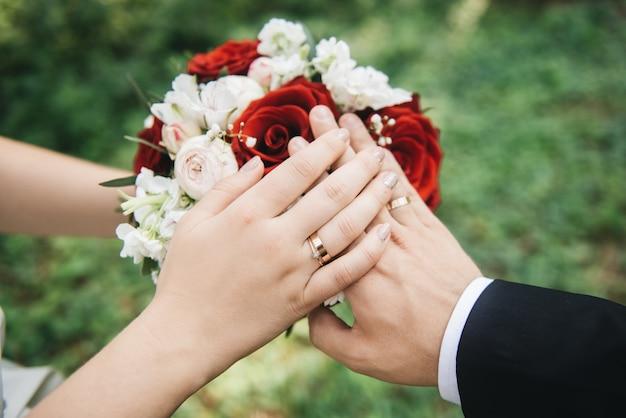 Mani degli sposi con fedi nuziali sul mazzo. sposa e sposo