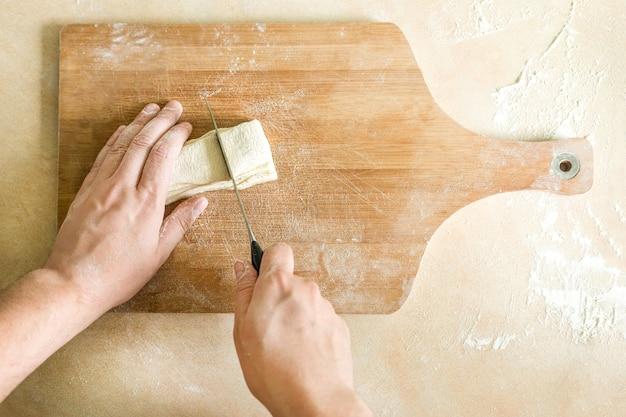 Mani degli uomini che tagliano pasta cruda