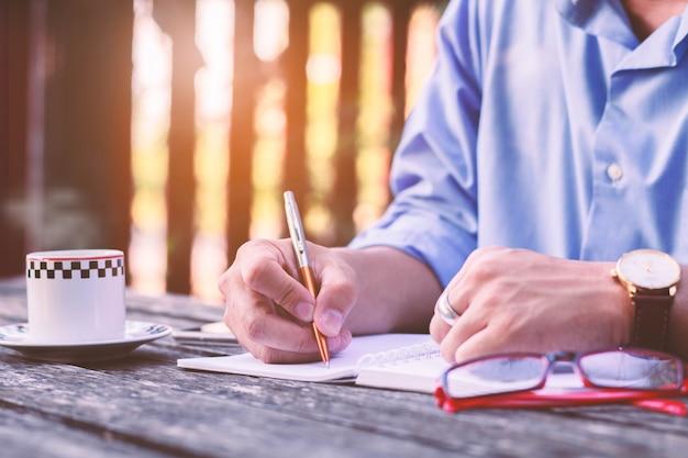 Mani degli uomini d'affari che scrivono sulla tavola di legno alla caffetteria.