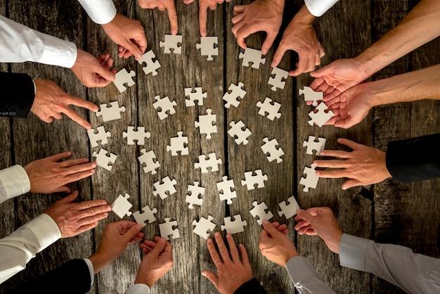 Mani degli uomini d'affari che tengono i pezzi di puzzle sulla tavola