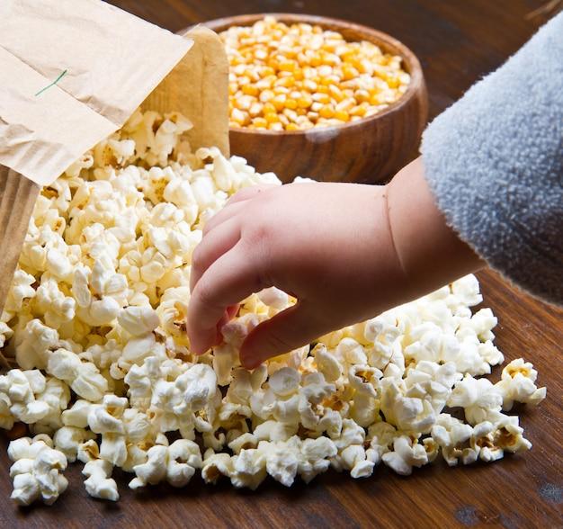 Mani dei bambini che mangiano popcorn