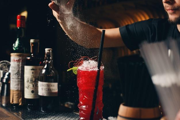 Mani dei baristi che spruzzano il succo nel bicchiere da cocktail pieno di bevande alcoliche