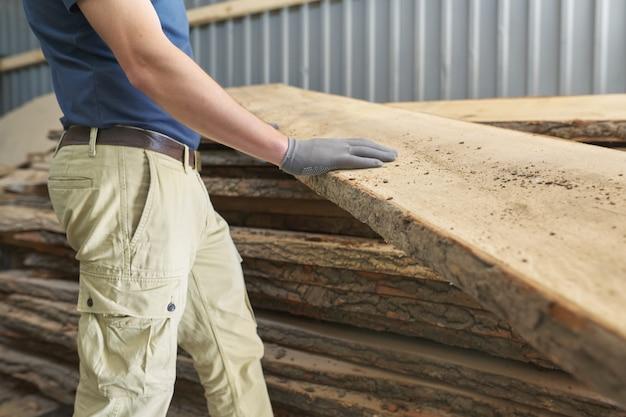 Mani dei carpentieri con il legno della plancia all'officina di falegnameria di carpenteria