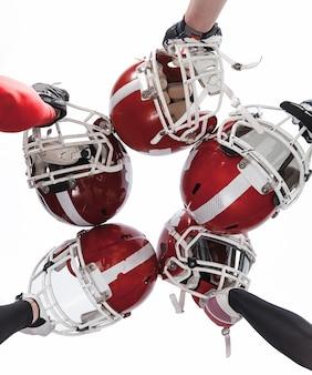 Mani dei giocatori di football americano con caschi su bianco